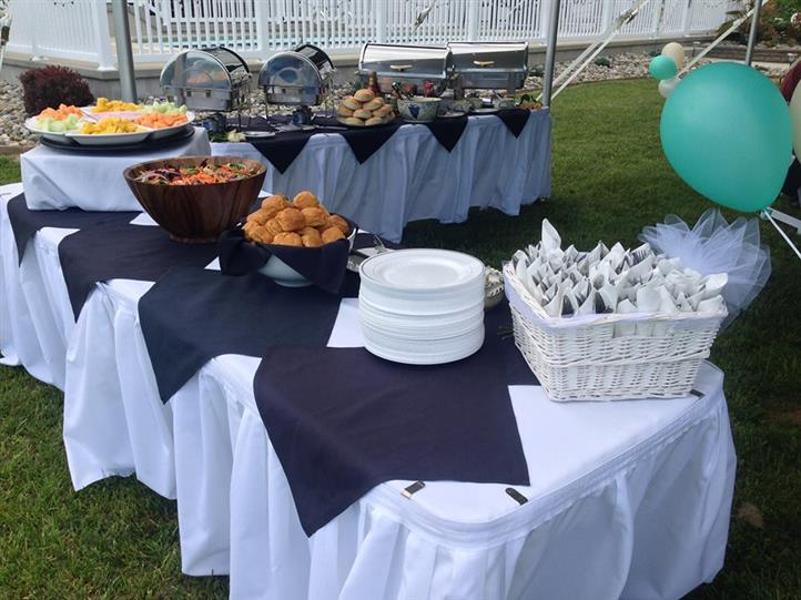 Outdoor covered catering tables with plates, cutlery, bread, salad, appetizers and sternos