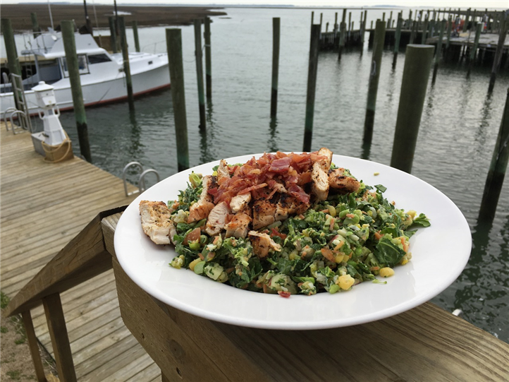 Chicken and bacon chopped salad on ledge of dock overlooking marina