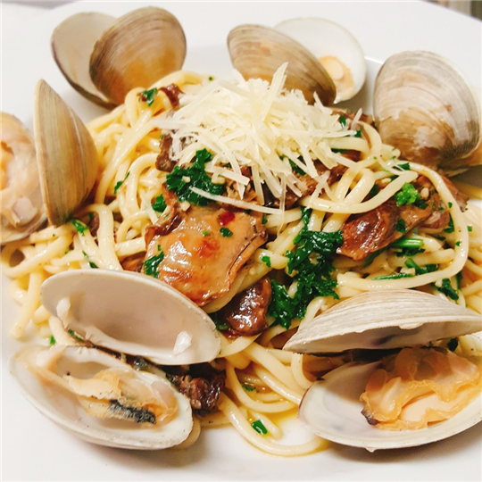 Smoked oysters and clam linguini. In-house brined and smoked oysters paired with juicy middleneck clams in a garlic wine sauce.