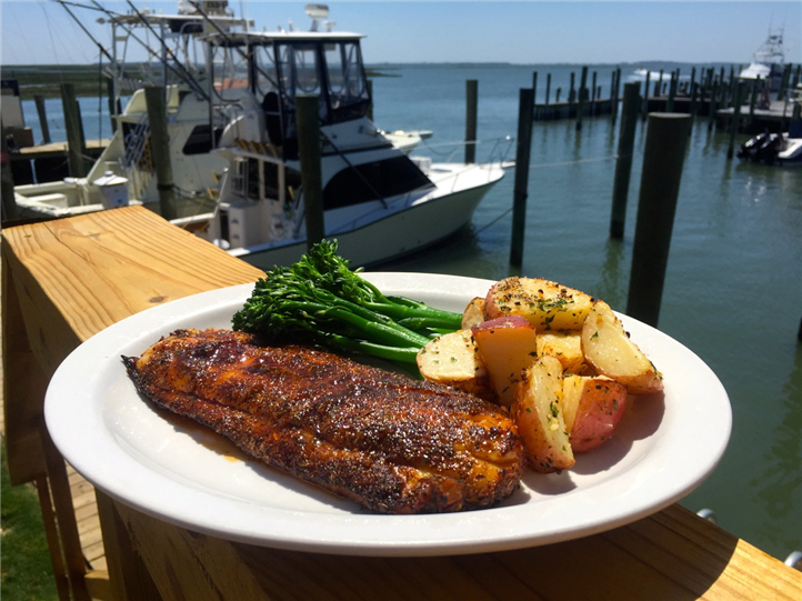 Fish filet with broccolini and potatoes on dish on ledge of dock overlooking boats in marina