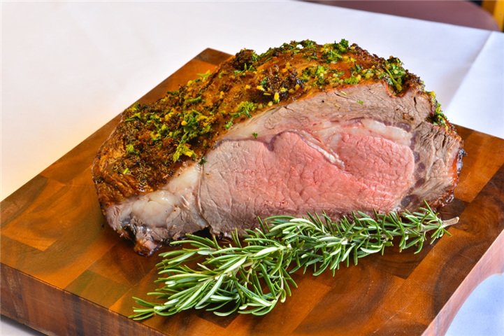Sliced beef tenderloin with rosemary leaf on wooden block