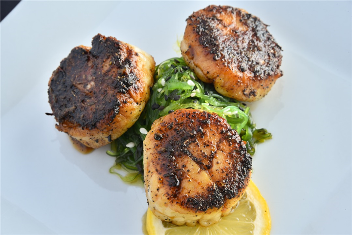 Fried sea scallops over greens