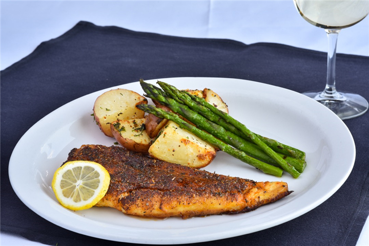 Fried fish with side of potatoes and asparagus on dish