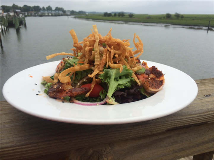 Grilled shrimp salad with wonton crisps on table overlooking marina