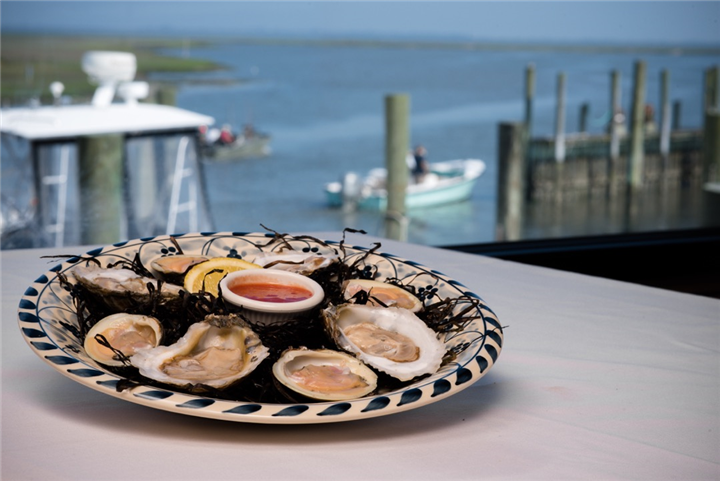 Plate of oysters on table overlooking marina