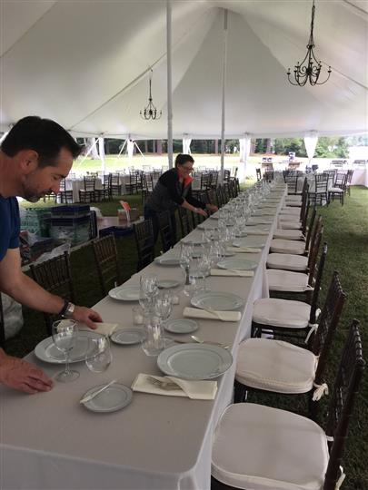 Man and woman setting up table with plates under tent