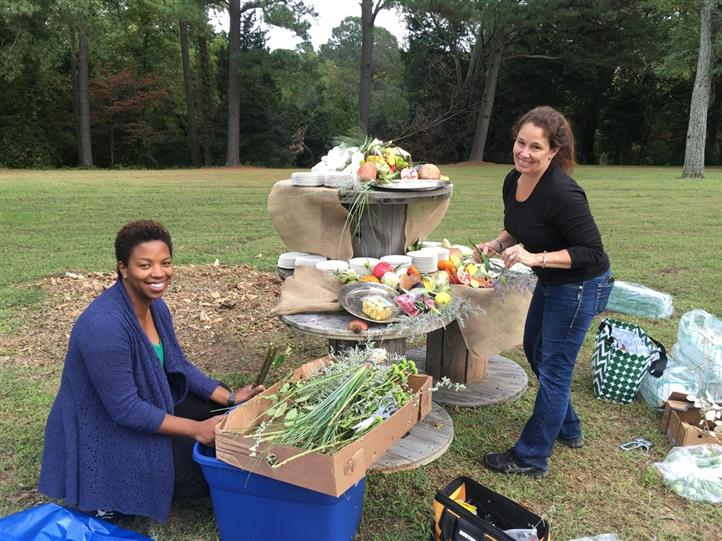 Women setting up catering display tables outdoors