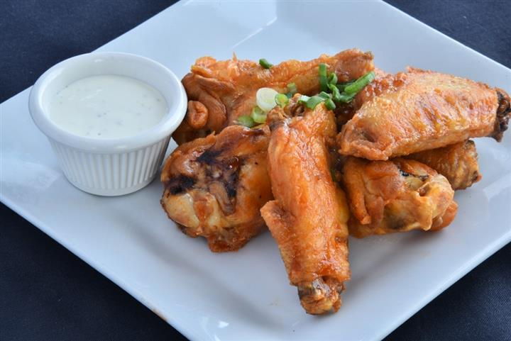 Six hot wings with ranch dressing for dipping on dish