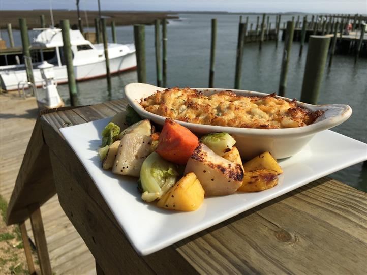 Broiled seafood with vegetables on dish on ledge of dock overlooking boats in marina