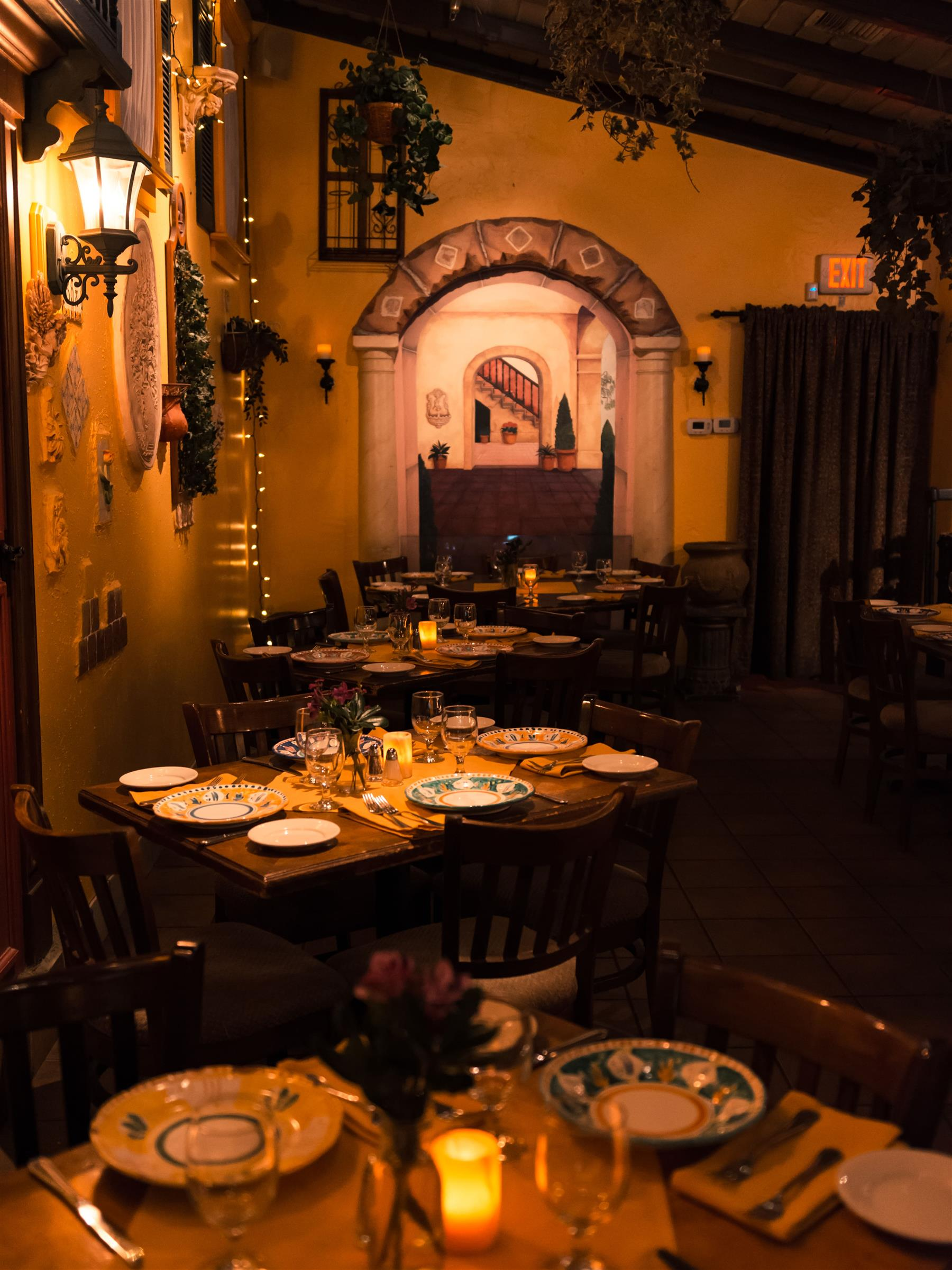 Wooden tables in a dim lit room with yellow stucco walls.
