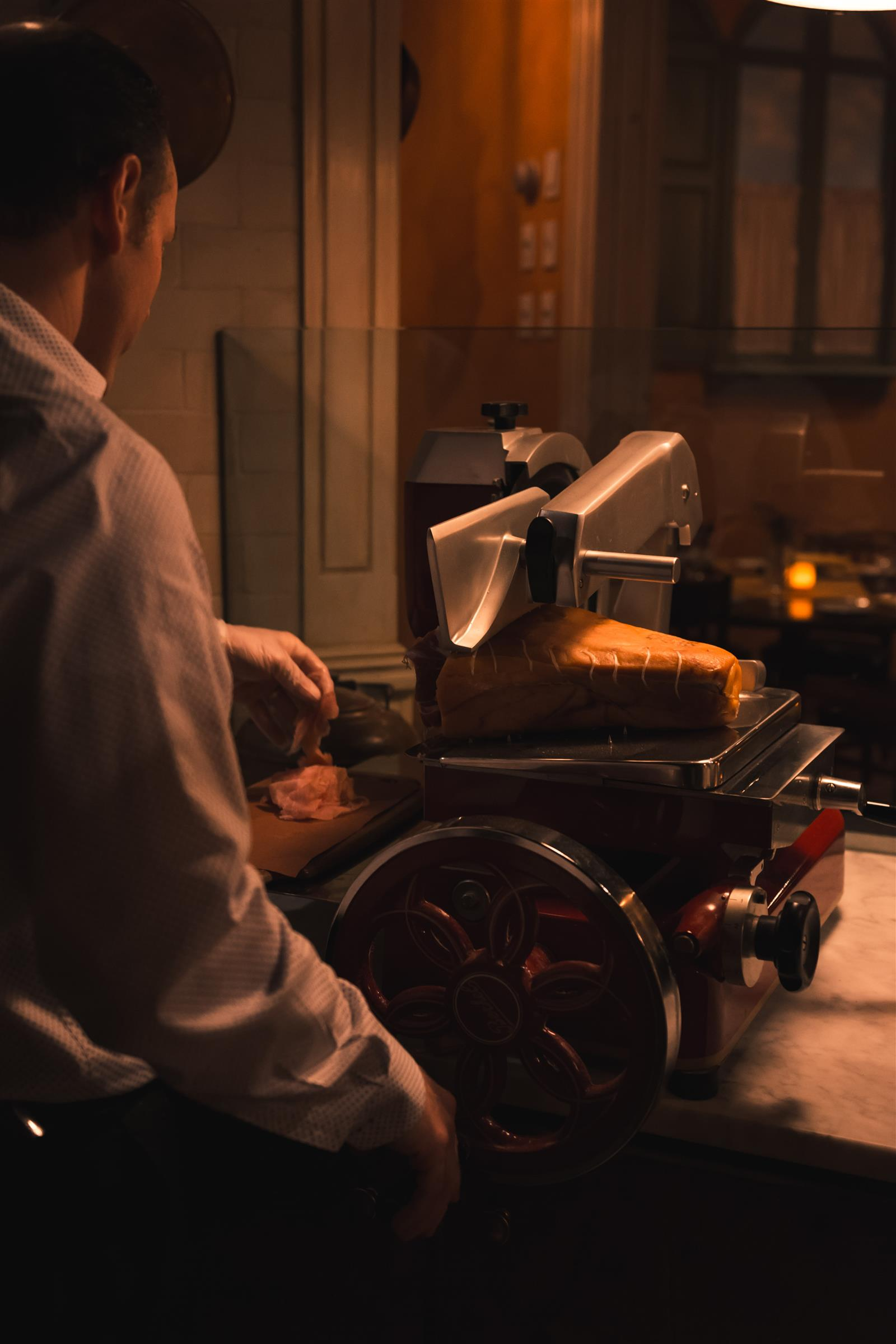 Man cutting proscuitto on old fashioned deli slicer