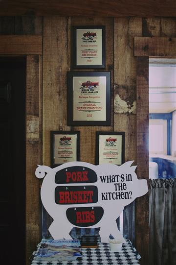 """a pig-shaped sign that reads, """"What's in the kitchen? Pork, Brisket, Ribs"""""""