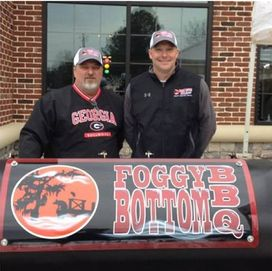 "two men stand proudly in front of a ""Foggy Bottom BBQ"" sign"
