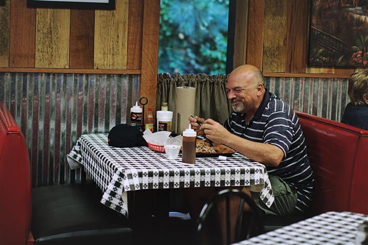 a man eating in a booth