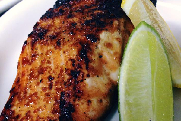 Closeup of blackened fish with lime wedge