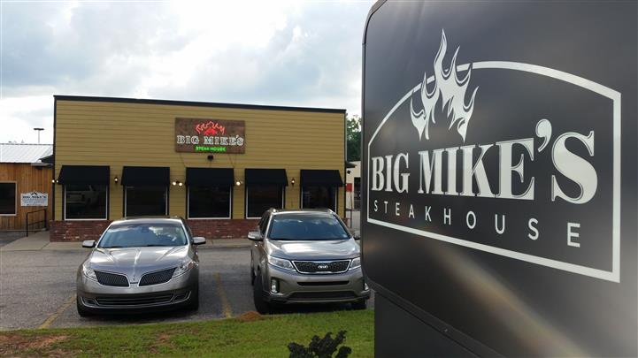 Big Mike's steakhouse sign in front of Big Mike's building and cars in parking lot