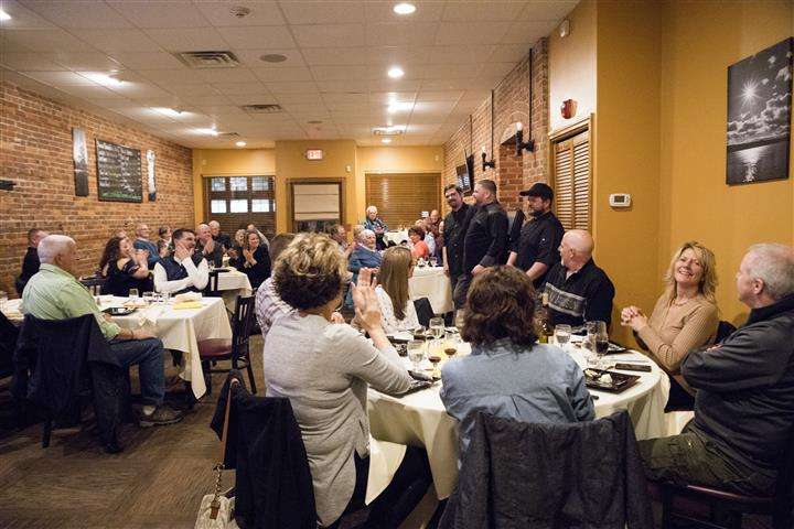 local event with a crowded dining area with various chefs speaking to the crowd