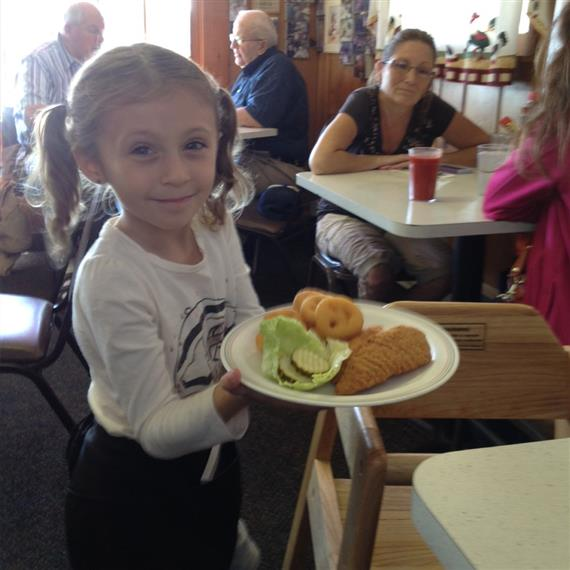 young girl holding plate of food