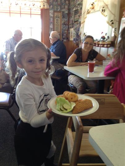 girl holding plate of chicken