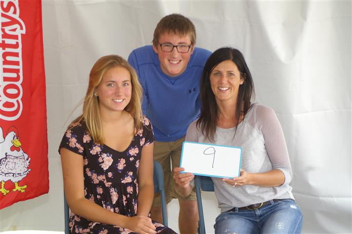 """family with sign that reads """"9"""""""