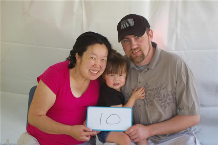 "family with sign that reads ""10"""