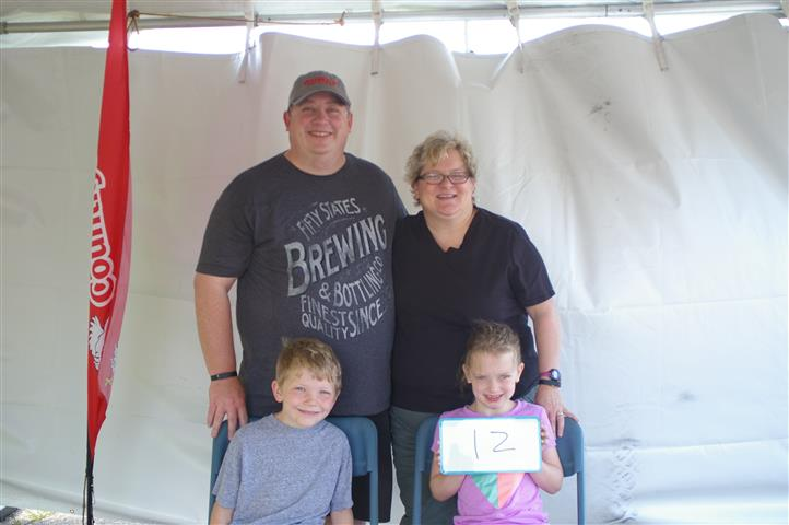 """family with sign that reads """"12"""""""