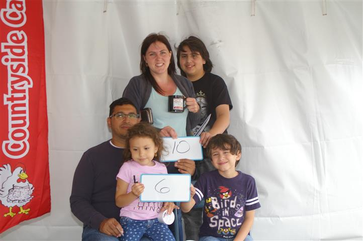 "family with signs that read ""10"" and ""6"""