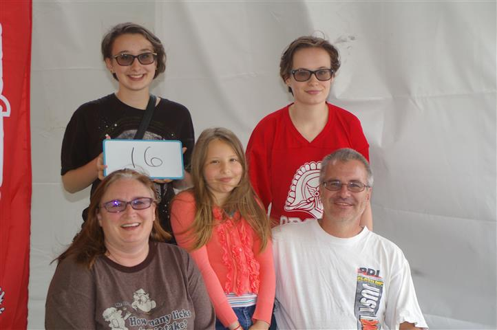 "family with sign that reads ""16"""