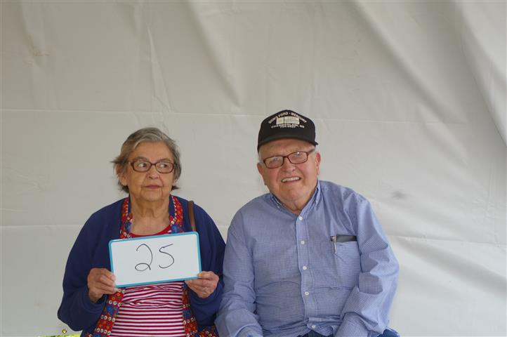 "couple with sign that reads ""25"""