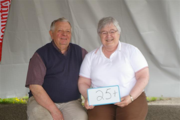 "couple with sign that reads ""25+"""
