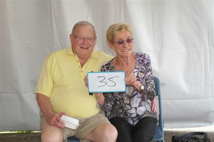 "couple holding sign that reads ""35"""