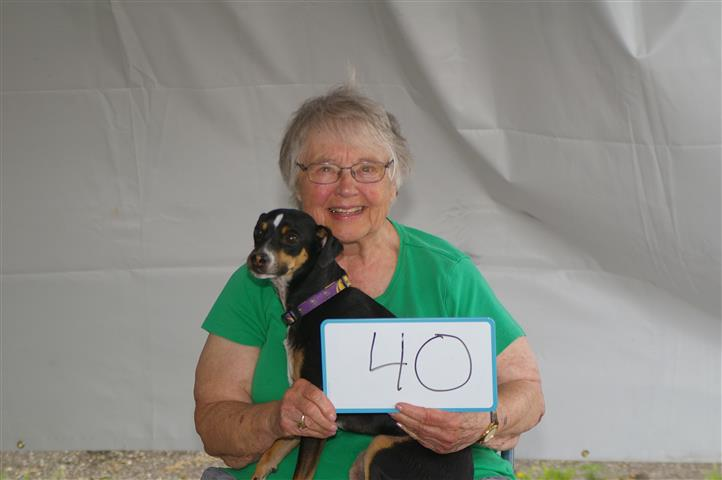 "woman with dog and sign that reads ""40"""