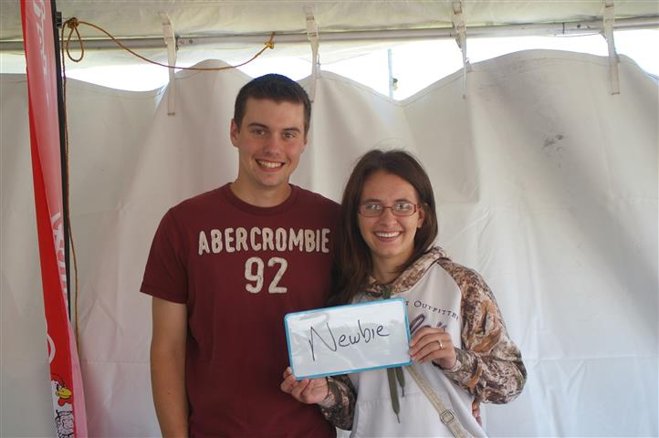 "couple holding sign that reads ""newbie"""