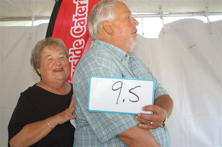 "couple holding sign that reads ""9.5"""