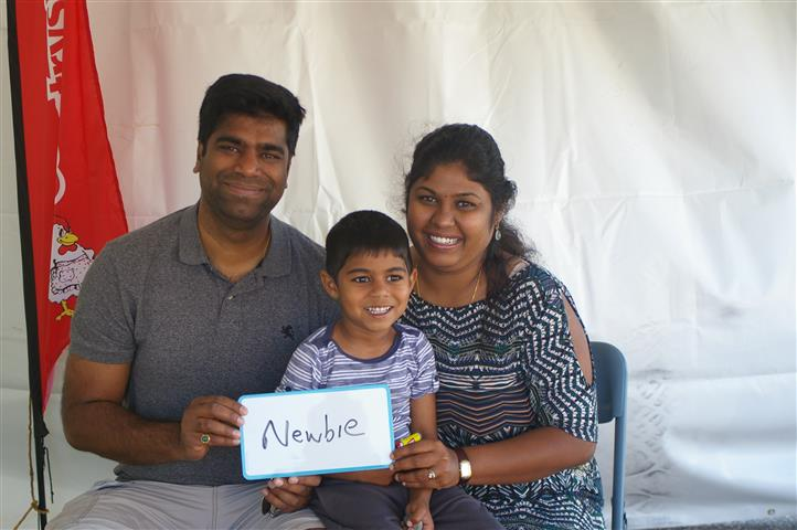 "family with sign that reads ""newbie"""