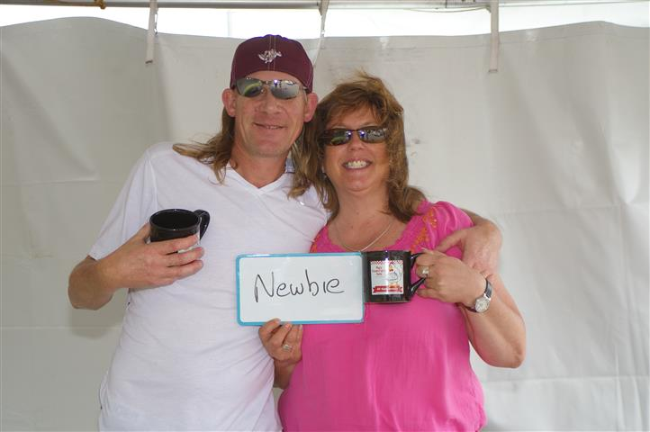 "couple holding a sign that reads ""newbie"""