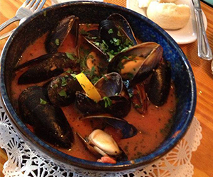 Black Chilean Mussels simmered in a white wine, tarragon, garlic, tomato, lemon and ginger brandy