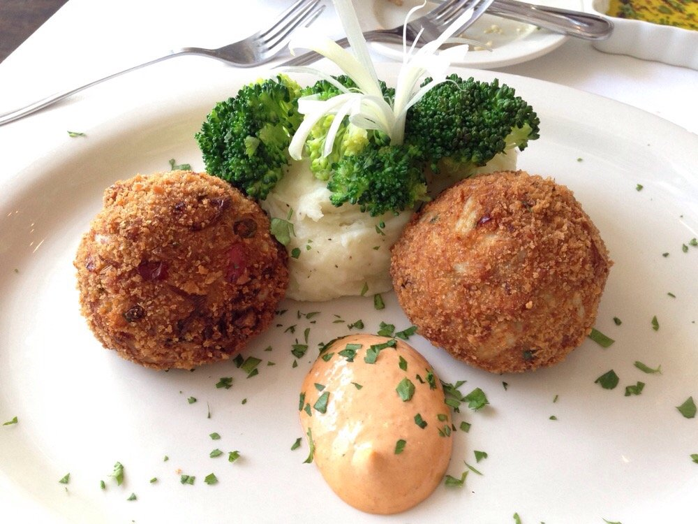 Mashed potatoes toped with broccoli with two rice balls and a creamy sauce on the side