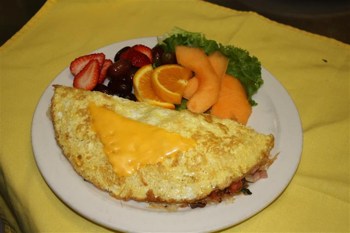 omlette filled with various meats and topped with cheese, with various side fruits