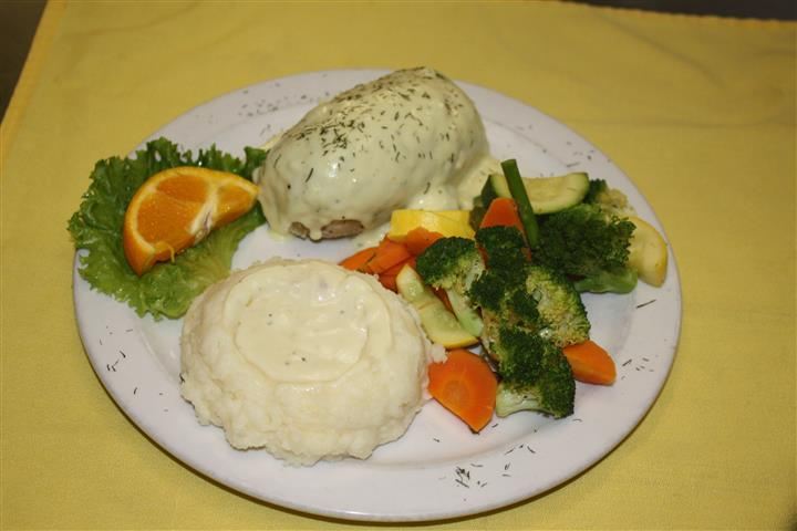 chicken cordon bleu with mashed potato side and various side vegetables
