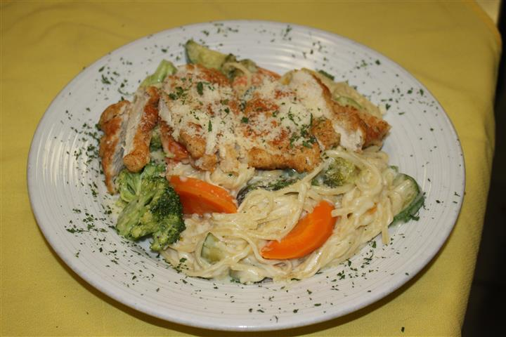 pasta in a cream sauce with chicken, broccoli and carrots