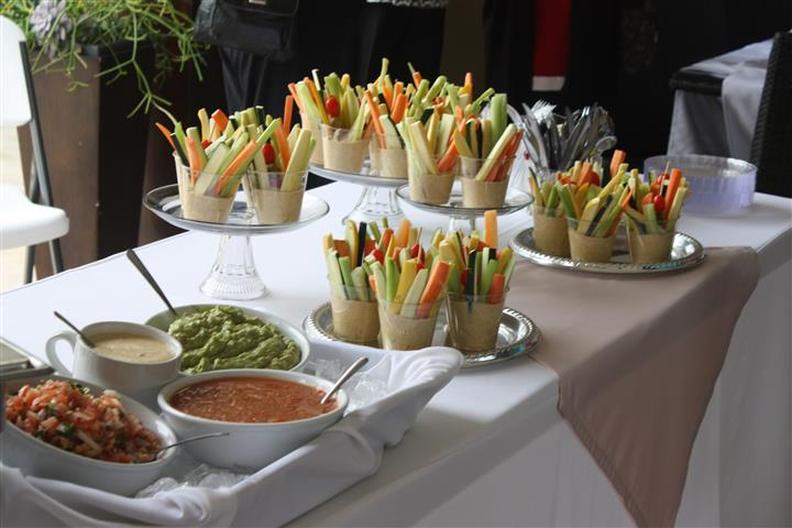 trays of various small vegetables in hummus, alongside a tray of various sides