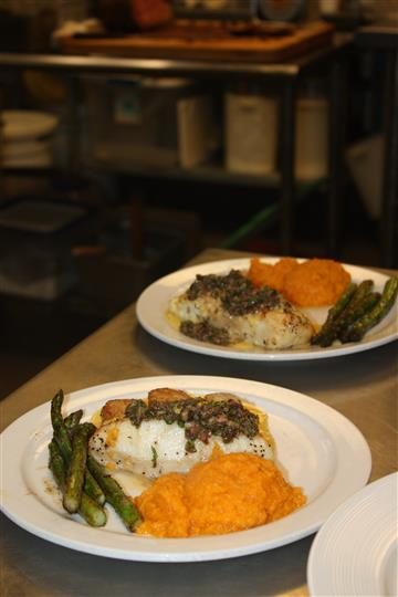 two plates of fish served with asparagus and sweet potatoes