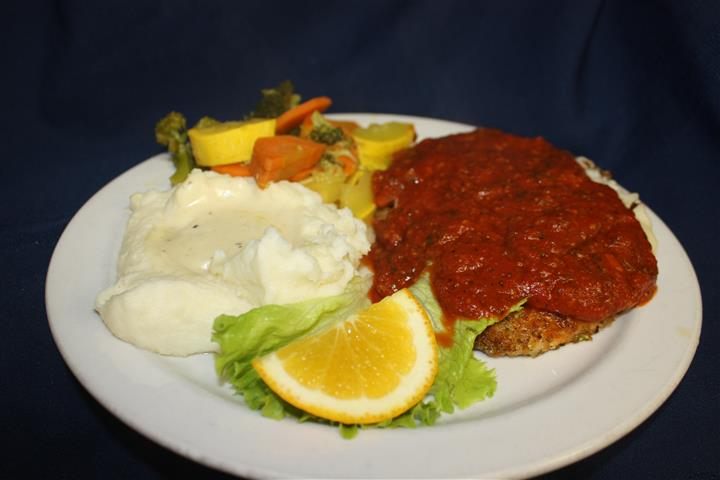 chicken parmesan covered in marinara sauce, with a side of mashed potatoes and sautéed vegetables