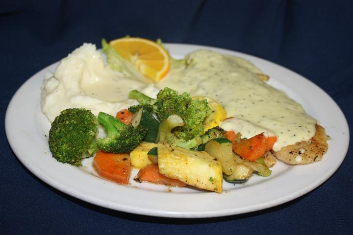 fish with a cream sauce, with a side of masheed potatoes and sautéed vegetables