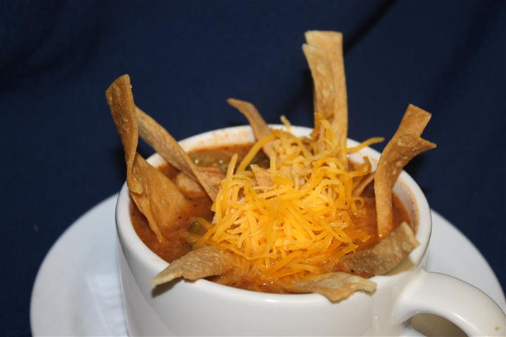 chili in a cup with cheese and chips