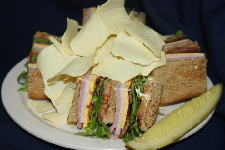 BLT sandwich sliced into quarters and covered in potato chips