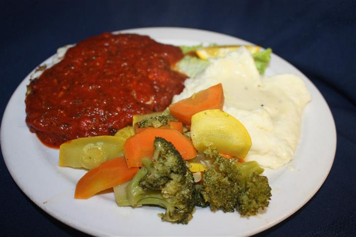 chicken parmesan covered in marinara sauce, with a side of mashed potatoes and steamed vegetables