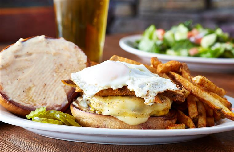 sandwich topped with a fried egg and served with french fries