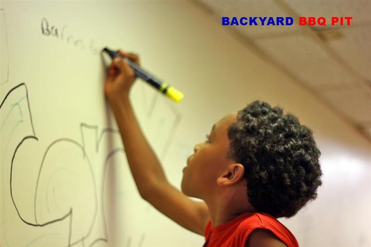 young child drawing on the walls of backyard bbq pit